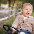 Stock Photo: Young Toddler Laughing and Playing on Toy Tractor Outside