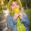 Young Girl Wearing Green Scarf and Hat Eating Apple Outside — Stok fotoğraf