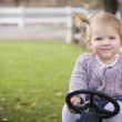 Young Toddler Smiling and Playing on Toy Tractor Outside — Stock Photo