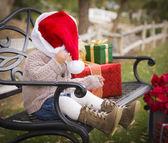Noel hediyeleri outsi ile oturup noel baba şapkası giyen genç çocuk — Stok fotoğraf