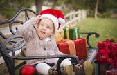 幼い子供のクリスマスのギフトのフェラと座っているサンタ帽子をかぶっています。 — Stock fotografie