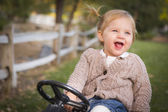 Young Toddler Laughing and Playing on Toy Tractor Outside — Stock Photo