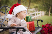 Young Child Wearing Santa Hat Sitting with Christmas Gifts Outsi — Stock Photo