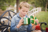 Suprised Young Boy Opens Christmas Gift Outside — Stock Photo