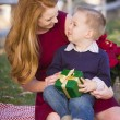 Young Boy Holding Christmas Gift with His Mom in Park — Stock Photo