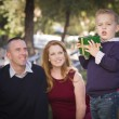 Young Boy Holding Christmas Gift in Park While Parents Look — Stock Photo #36052171