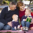 Small Young Family Opening Christmas Gifts in the Park — Stock Photo #36052183