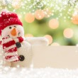 Snowman with Blank White Card Over Abstract Snow and LIght — Stock Photo #36431677