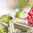 Stack of Hundred Dollar Bills with Bow Near Christmas Ornaments — Stock Photo #36431799
