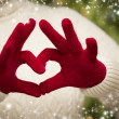 Woman Wearing Red Mittens Holding Out a Heart Hand Sign — Stok fotoğraf