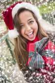 Pretty Woman Wearing a Santa Hat with Wrapped Gift — Stock Photo
