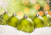 Green Christmas Ornaments on Snow Over an Abstract Background — Stock Photo