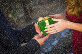 Hands of Man and Woman Exchanging Christmas Gift in Snow — Stock Photo