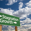 Stock Photo: Stagnation or Growth Green Road Sign Over Clouds and Sky