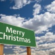 Stock Photo: Merry Christmas Green Road Sign Over Clouds and Sky