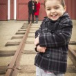 Stock Photo: Mixed Race Boy at Train Depot with Parents Smiling Behind