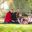 Mixed Race Family Enjoying Christmas Gifts in the Park Together — Stock Photo #36901619