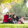 Mixed Race Family Enjoying Christmas Gifts in the Park Together — Stock Photo
