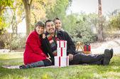 混合レース家族一緒に公園にクリスマス プレゼントを楽しんで — ストック写真