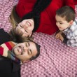 Stock Photo: Family in Winter Clothing Laying on Their Backs in Park