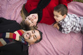 Family in Winter Clothing Laying on Their Backs in Park — Stock Photo