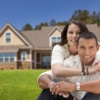 Happy Hispanic Young Couple in Front of Their New Home — Stock Photo #37189437