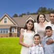 Stock Photo: Young Hispanic Family in Front of Their New Home