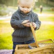 Blonde Baby Boy Opening Picnic Basket Outdoors at the Park — Stock Photo #37557909