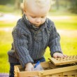 Blonde Baby Boy Opening Picnic Basket Outdoors at the Park — Stock Photo #37557913
