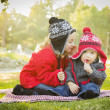 Little Girl Whispers A Secret to Baby Brother Outdoors — Stock Photo #37557965