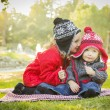Little Girl Whispers A Secret to Baby Brother Outdoors — Stock Photo