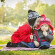 Little Girl Whispers A Secret to Baby Brother Outdoors — Stock Photo #37557989