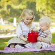 Little Girl Gives Her Baby Brother A Gift at Park — Photo