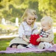 Little Girl Gives Her Baby Brother A Gift at Park — Stock Photo