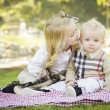Sweet Little Girl Kisses Her Baby Brother at the Park — Stock Photo