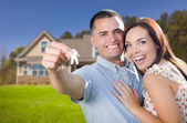 Casal militar com chaves de casa na frente de casa nova — Fotografia Stock
