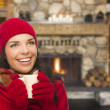 Stok fotoğraf: Mixed Race Girl Enjoying Warm Fireplace and Holding Mug
