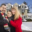Stock Photo: Mixed Race Family in Front of House in The Snow