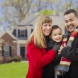 Stock Photo: Happy Mixed Race Family in Front of House