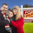 Family in Front of Sold Real Estate Sign and House — Stock Photo #37722511