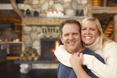 Affectionate Couple at Rustic Fireplace in Log Cabin — Stock Photo