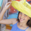 Pretty Girl Tries on Yellow Hat at Market — Stock Photo