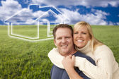 Happy Couple Hugging in Grass Field with Ghosted House Behind — Stock Photo