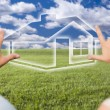 Stock Photo: Couple Framing Hands Around House Figure in Grass Field