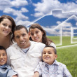 Hispanic Family Sitting in Grass Field with Ghosted House Behind — Foto Stock