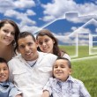 Hispanic Family Sitting in Grass Field with Ghosted House Behind — Stock Photo