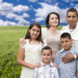 Hispanic Family Portrait Standing in Grass Field — Stock Photo