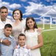 Foto Stock: Hispanic Family Standing in Grass Field with Ghosted House Behin
