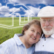 Senior Couple Standing in Grass Field with Ghosted House Behind — Stock Photo #38920151