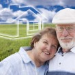 Stock Photo: Senior Couple Standing in Grass Field with Ghosted House Behind